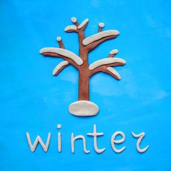 Albero di plastilina nella neve e la parola inverno su uno sfondo blu