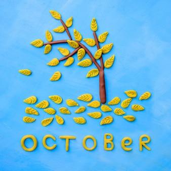 Albero giallo di autunno del plasticine e la parola ottobre