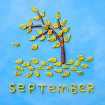 Albero giallo di autunno del plasticine e la parola settembre