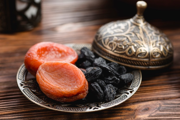 Albicocca secca e uva passa nera sul piatto metallico con coperchio sullo scrittorio di legno