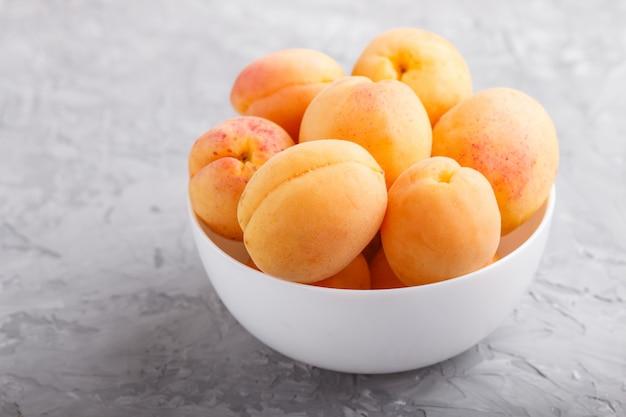 Albicocche arancioni fresche in ciotola bianca. vista laterale.