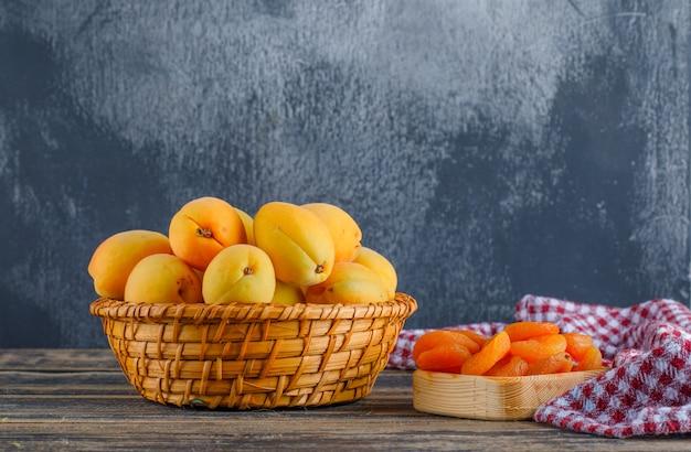 Albicocche con albicocche secche, panno da picnic in un cesto di vimini su gesso e tavolo in legno, vista laterale.