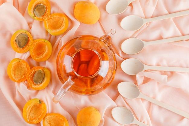 Albicocche con tè, cucchiai di legno distesi