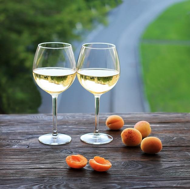 Albicocche e due bicchieri di vino bianco