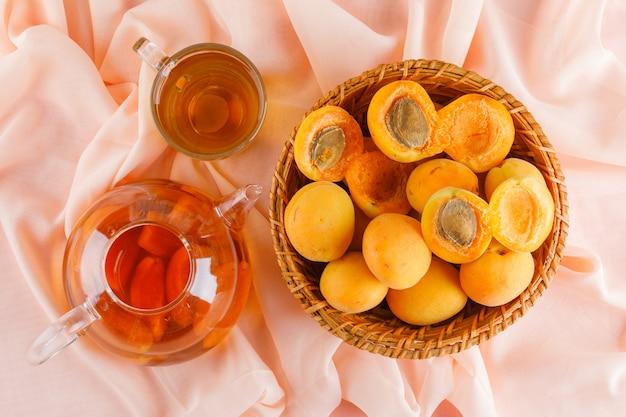 Albicocche in un cesto di vimini con tè piatto disteso