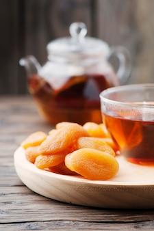 Albicocche secche dolci con una tazza di tè nero