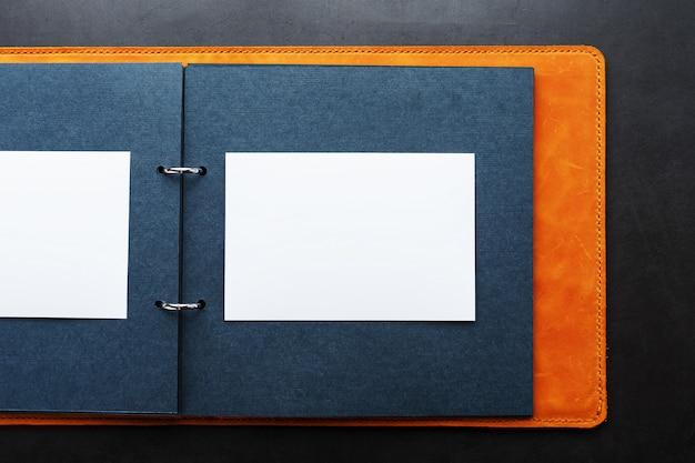 Album fotografico con spazio vuoto per foto, cornici bianche su carta nera.
