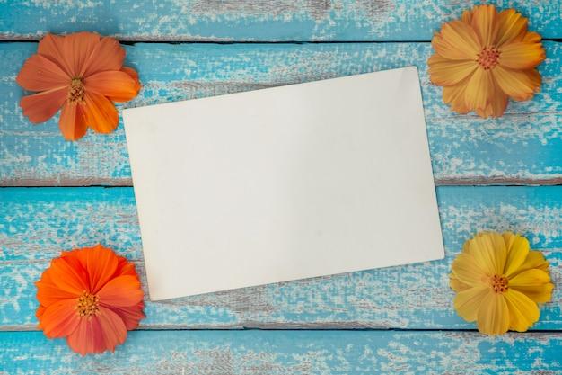 Album in bianco della struttura della foto con il fiore su vecchio fondo di legno blu