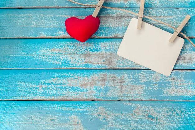 Album in bianco della struttura della foto e cuore rosso che appendono sul fondo di legno blu d'annata