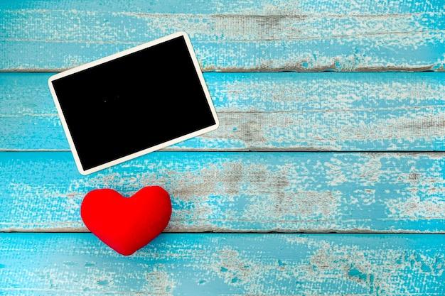 Album in bianco della struttura della foto e cuore rosso su fondo di legno blu d'annata