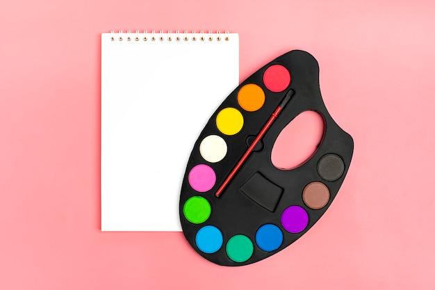 Album per disegno, tavolozza di colori colorati su un rosa ritorno a scuola