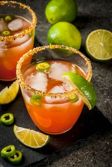 Alcol. cocktail sudamericano messicano tradizionale. michelada piccante con peperoncini jalapeno caldi e lime. su un tavolo di pietra scura. copyspace