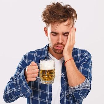 Alcol. ragazzo in camicia blu con birra