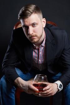 Alcolismo maschile, uomo con un bicchiere di alcol in mano. malattia della dipendenza alcolica, cattiva abitudine, sollievo dallo stress attraverso l'alcol. alcolista anonimo