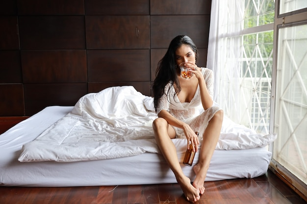 Alcool bevente della donna asiatica ubriaca mentre sedendosi nel letto
