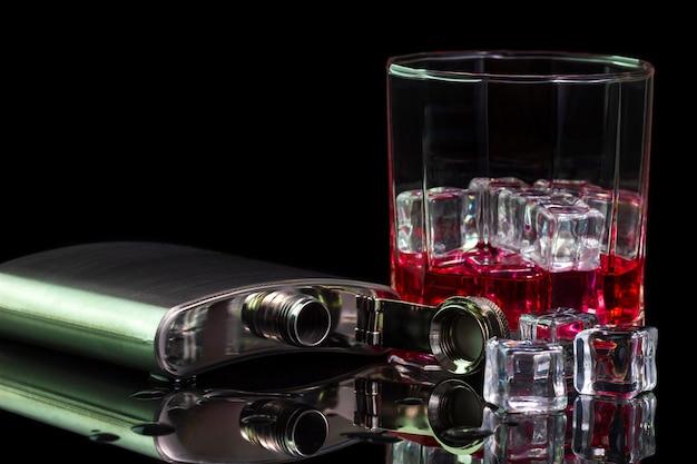 Alcool e ghiaccio del liquore della boccetta dell'acciaio inossidabile sulla tavola con whiskey rosso in vetro sul fondo di oscurità