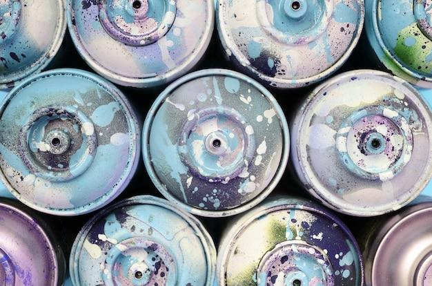 Alcune bombolette spray usate con gocce di vernice blu si trovano sulla trama della carta di colore blu pastello di moda
