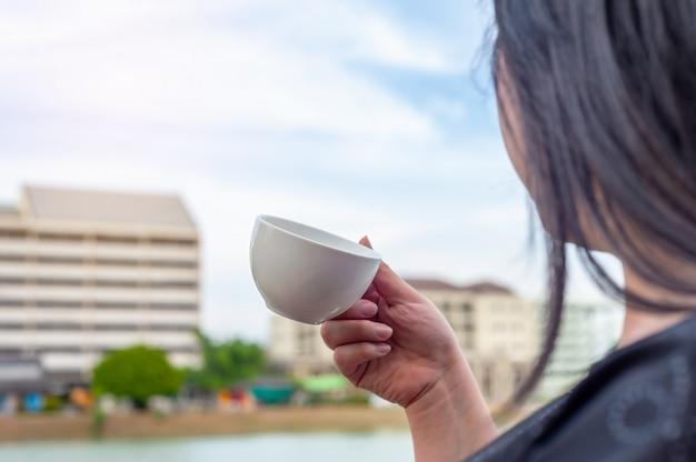 Alcune donne con la tazza di caffè sulla costruzione della torre offuscata