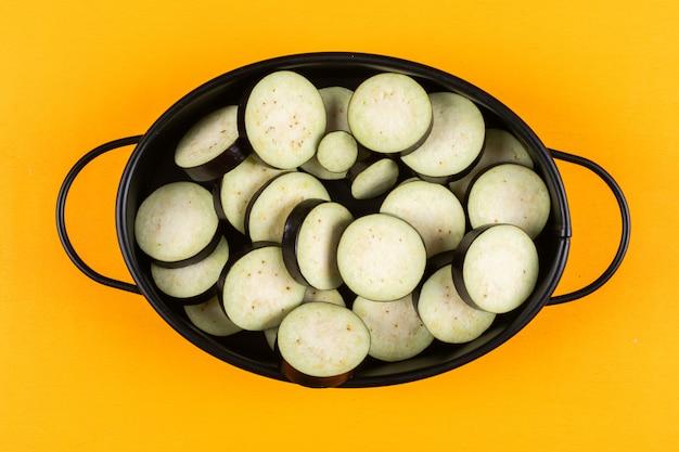 Alcune fette di melanzane in una pentola su sfondo giallo, piatto laici.