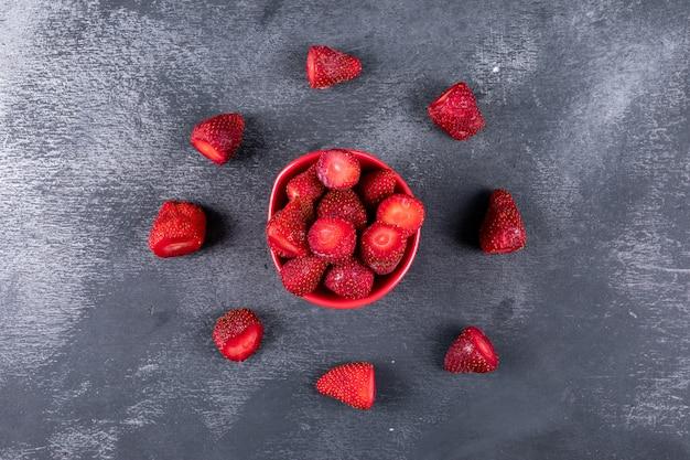 Alcune fragole con altre che formano il cerchio intorno in una ciotola sul tavolo scuro, vista dall'alto.