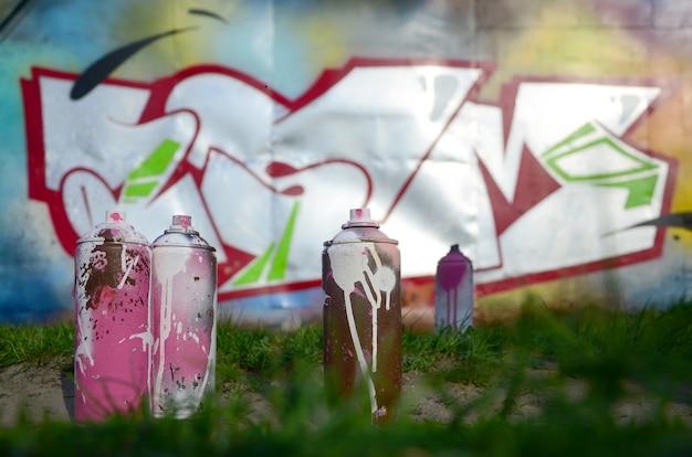 Alcune lattine di vernice usate giacciono a terra vicino al muro con un bellissimo dipinto di graffiti.