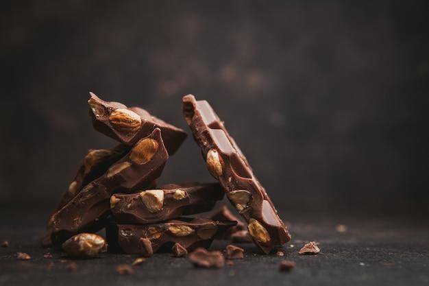 Alcune mandorle con cioccolato su marrone scuro, vista laterale. spazio per il testo