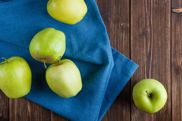 Alcune mele verdi sul panno blu e sul fondo di legno, vista superiore.