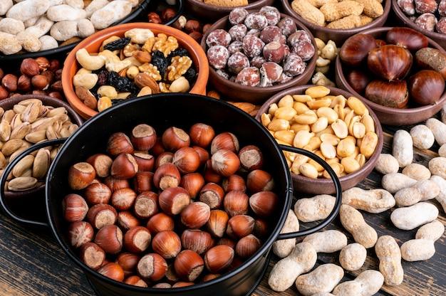 Alcune noci assortite e frutta secca con noci pecan, pistacchi, mandorle, arachidi, anacardi, pinoli in diverse ciotole e padella nera