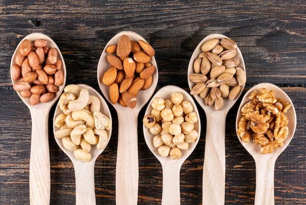 Alcune noci assortite e frutta secca con noci pecan, pistacchi, mandorle, arachidi, anacardi, pinoli in un cucchiaio di legno
