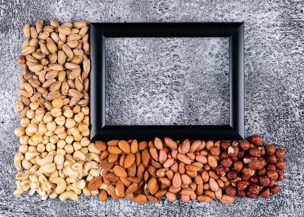 Alcune noci diverse con cornice nera per il tuo testo: noci pecan, pistacchi, mandorle, arachidi, anacardi