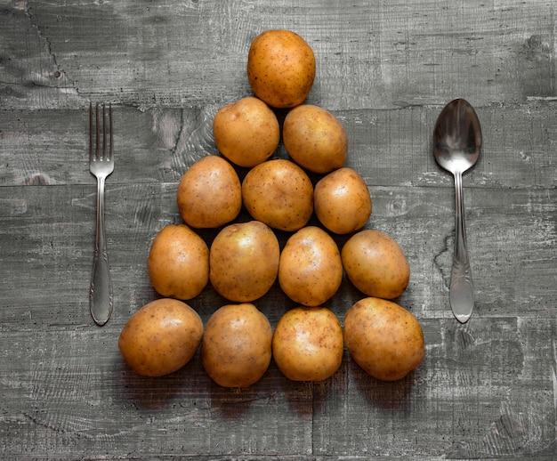 Alcune patate su un vecchio tavolo di legno o una superficie di legno sono disposte a forma di albero di natale. vista dall'alto del layout