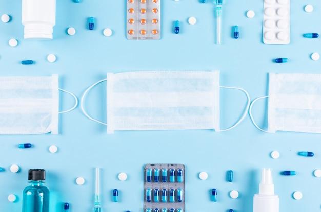 Alcune pillole si diffondono con maschere, spray, bottiglia di pillola, aghi su sfondo azzurro chiaro, vista dall'alto.