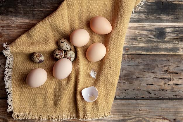 Alcune uova con quella rotta sul panno e sul fondo di legno scuro, vista superiore.