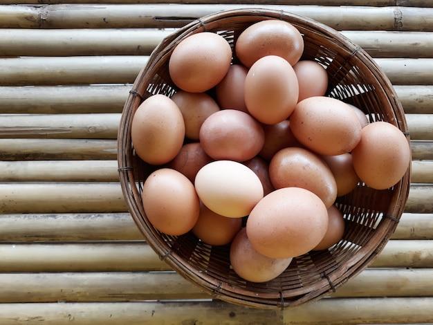 Alcune uova di gallina nel cestino sul tavolo di bambù