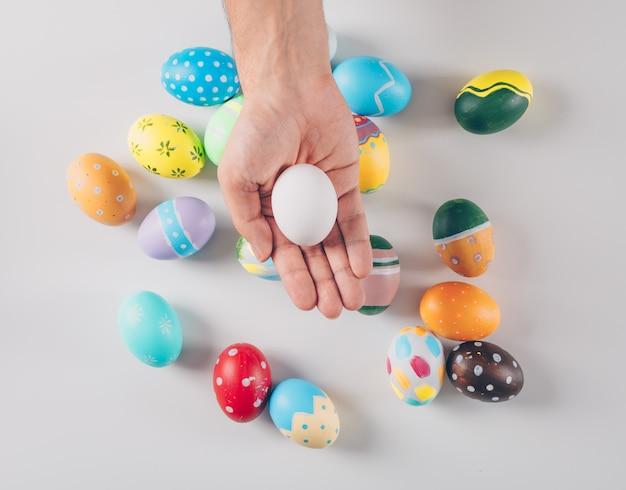 Alcune uova di pasqua con l'uomo che tiene un uovo bianco su fondo bianco, vista superiore.