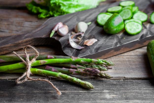Alcuni asparagi con cetriolo affettato, aglio, lattuga in un tagliere su fondo di legno scuro, vista dell'angolo alto.