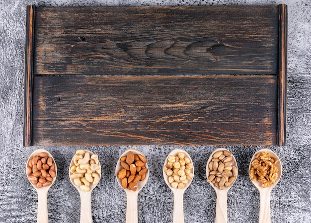 Alcuni assortiti di noci e frutta secca con noci pecan, pistacchi, mandorle, arachidi, in un cucchiaio di legno sul tagliere di legno