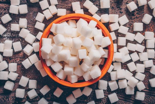 Alcuni cubi dello zucchero bianco in una ciotola arancio sulla tavola di legno scura, disposizione piana.