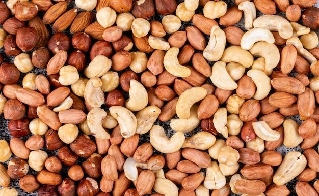Alcuni dei diversi tipi di noci con noci pecan, pistacchi, mandorle, arachidi, anacardi, pinoli close-up.