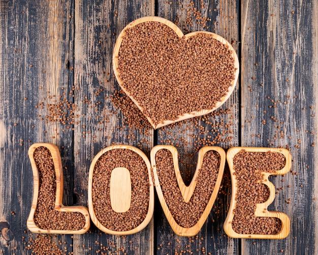 Alcuni grano saraceno su forma di cuore e la parola amore su fondo di legno scuro, vista dall'alto.