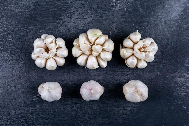 Alcuni grappoli d'aglio erano allineati sul tavolo scuro strutturato, piatto disteso.
