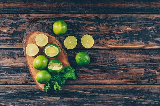 Alcuni limoni verdi con le fette e le foglie sulla fetta di legno e sul fondo di legno scuro, disposizione piana. spazio per il testo
