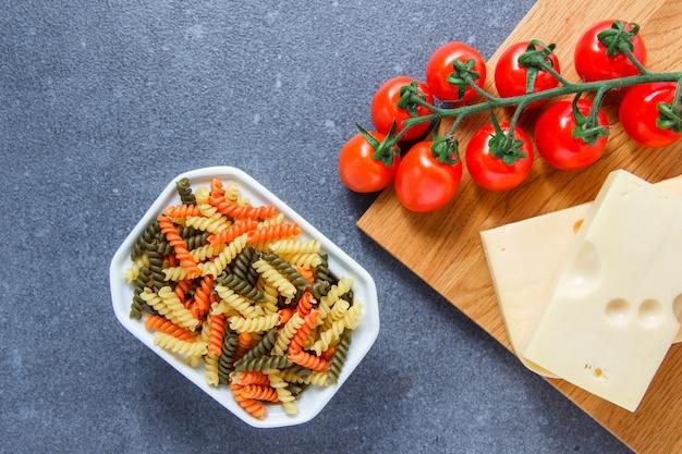 Alcuni maccheroni colorati pasta con pomodori, formaggio in una ciotola sulla superficie grigia, vista dall'alto.