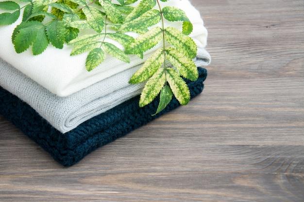 Alcuni maglioni a maglia caldi impilati. prossime foglie d'autunno. il concetto di caldo