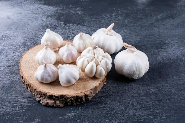 Alcuni mazzi di aglio su un troncone di legno e nelle vicinanze sul tavolo scuro strutturato