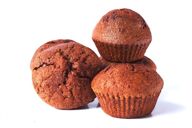 Alcuni muffin della pasta di cioccolato fondente sopra isolati su fondo bianco.