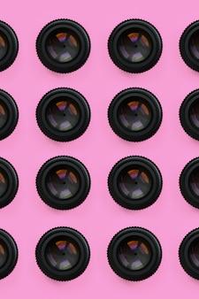 Alcuni obiettivi della fotocamera con un'apertura chiusa giacciono sullo sfondo della trama del colore rosa pastello