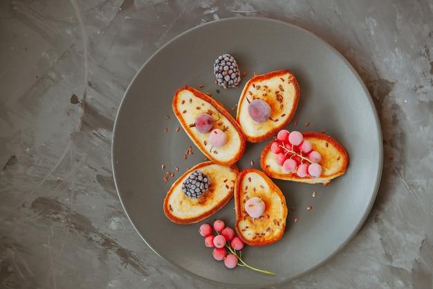 Alcuni pancake con le more e i mirtilli rossi in un piatto sulla tavola strutturata, vista superiore.