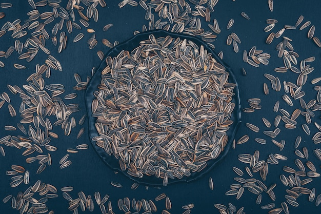 Alcuni semi di girasole neri in un piatto su fondo nero, vista superiore.