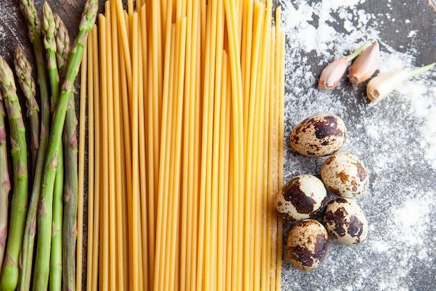 Alcuni spaghetti con asparagi, uova e aglio su sfondo scuro con texture, vista dall'alto.